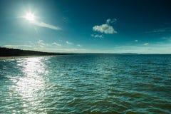 Océano azul y cielo soleado con las nubes Fotos de archivo libres de regalías