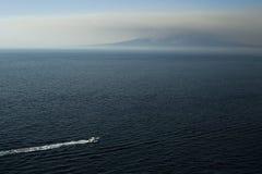 Océano, barco en el mar, agua, montaña en el fondo del mar imágenes de archivo libres de regalías