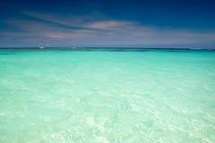 Océano ciánico bajo el cielo azul con las nubes Foto de archivo