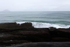 Océano con las ondas que se estrellan en piedras imagen de archivo
