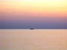 Océano Pacífico con horizonte claro, los cielos púrpuras de la puesta del sol y la nave en horizonte Foto de archivo libre de regalías