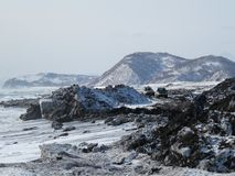 Océano Pacífico, ondas y vistas de la colina nevada en invierno en tiempo soleado en Kamchatka, Rusia imagen de archivo libre de regalías
