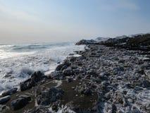 Océano Pacífico, ondas y vistas de la colina nevada en invierno en tiempo soleado en Kamchatka, Rusia foto de archivo libre de regalías