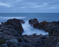 Oc?ano pageful azul entre las rocas negras imágenes de archivo libres de regalías