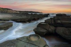 Océano que fluye dentro y fuera del abismo Norah Head de la roca Foto de archivo