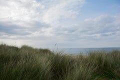 Océano y la playa en la manera atlántica salvaje de detrás las dunas imagenes de archivo
