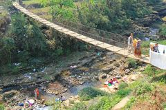 过一座吊桥的Ocal人在尼泊尔 免版税图库摄影