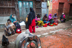 Ocal people sit in the street. The caste system is still intact today but the rules are not as rigid as they were in the past. BHAKTAPUR, NEPAL - CIRCA DEC Royalty Free Stock Photos