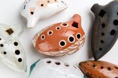 Ocarinas on white background. Orange color ocarina in glaze. Royalty Free Stock Images