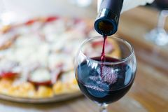 Ocasión especial para la celebración - el vino rojo se vierte de la botella en el vidrio en restaurante o café imagen de archivo