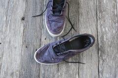 Ocasionais velhos desvanecem-se sapatas azuis com laço no fundo de madeira Foto de Stock