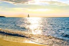 Ocaso de oro hermoso sobre el mar con la nave en horisont Foto de archivo libre de regalías
