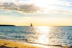 Ocaso de oro hermoso sobre el mar con la nave en horisont Fotos de archivo libres de regalías