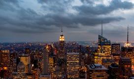 Ocaso desde arriba de la roca - Empire State Building se encendió en el centro del bastidor - en color imagen de archivo