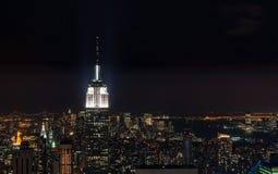 Ocaso desde arriba de la roca - pináculo del Empire State Building encendido brillantemente a la izquierda del marco - en color foto de archivo