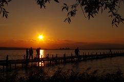 Ocaso en el lago con la gente Fotos de archivo