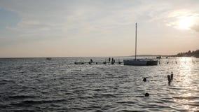 Ocaso, sol hermoso que sube sobre el río en la cámara lenta, gente en la pesca, seres humanos de la silueta en el embarcadero en  metrajes