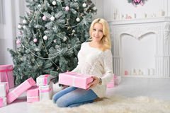 The occasion when presented with gifts. Girl sitting on the floor next to the Christmas tree and the mountain of wrapped boxes, holding a box wrapped in paper Royalty Free Stock Photo