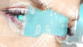 Occhi che esaminano interfaccia olografica con il codice binario stock footage