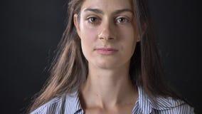 Occhi d'apertura di marrone della giovane donna affascinante ed esaminare macchina fotografica, isolata sul fondo nero dello stud stock footage