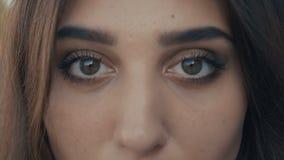 Occhi del primo piano del modello castana della bella giovane donna che esamina la macchina fotografica Ragazza con i grandi occh archivi video