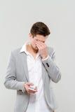 Occhi depressi del cellulare e dello sfregamento della tenuta del giovane Fotografia Stock Libera da Diritti