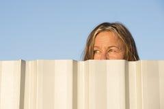 Occhi di sorveglianza della donna dietro il recinto all'aperto Immagine Stock