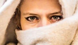 Occhi di una donna in una sciarpa capa immagini stock