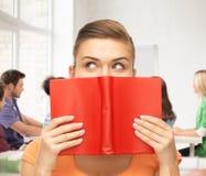 Occhi e mani della donna che tengono libro rosso Fotografia Stock Libera da Diritti