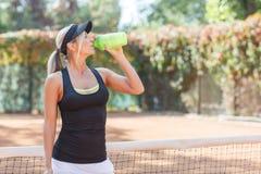 Occhi femminili abbastanza giovani dell'acqua potabile del giocatore di tennis chiusi Fotografia Stock Libera da Diritti