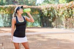 Occhi femminili abbastanza giovani dell'acqua potabile del giocatore di tennis chiusi Fotografia Stock