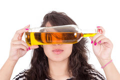 Occhi nascondentesi della ragazza latina dietro una bottiglia gialla Fotografia Stock Libera da Diritti
