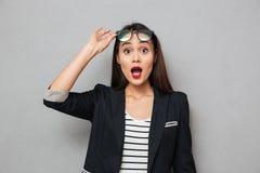Occhiali asiatici colpiti della tenuta della donna di affari ed esaminare macchina fotografica Fotografie Stock