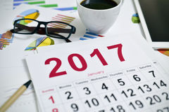 Occhiali, caffè, grafici della compressa e calendario 2017 Fotografia Stock