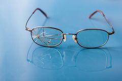 Occhiali con la lente incrinata su fondo blu brillante Fotografie Stock