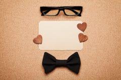 Occhiali, cravatta a farfalla e spazio in bianco di carta vuoto nel giorno di padri felice, fondo del bordo del sughero, vista su Fotografie Stock