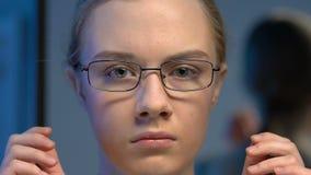 Occhiali d'uso dell'adolescente femminile insicuro, effetto defocused di visione, primo piano archivi video