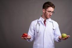 Occhiali d'uso di giovane medico bello dell'uomo contro backgr grigio fotografie stock