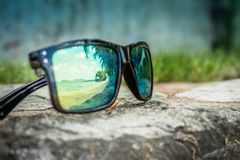 Occhiali da sole alla moda Occhiali da sole con le lenti rispecchiate Riflessione della spiaggia e delle palme tropicali in occhi fotografia stock libera da diritti
