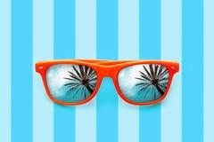 Occhiali da sole arancio di estate con le riflessioni delle palme isolati nel fondo blu pastello con le bande Fotografia Stock