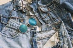 Occhiali da sole blu d'avanguardia del cerchio sui jeans e sul rivestimento Fotografia Stock