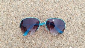 Occhiali da sole blu nella sabbia immagini stock