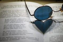 Occhiali da sole blu rotondi su un libro aperto immagini stock