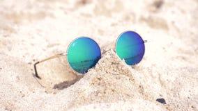 Occhiali da sole che si trovano sulla sabbia sulla spiaggia Gli occhiali da sole riflettono il mare, il sole, il cielo, la spiagg stock footage
