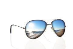 Occhiali da sole con la riflessione della spiaggia sopra bianco Fotografie Stock