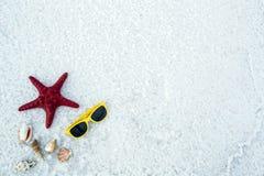 Occhiali da sole, coperture e stelle marine su un fondo bianco Immagini Stock