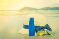 Occhiali da sole, crema del sole e cappello sulla spiaggia di sabbia bianca Immagine Stock
