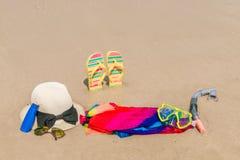 Occhiali da sole, crema del sole e cappello sulla spiaggia di sabbia bianca Fotografia Stock