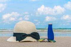 Occhiali da sole, crema del sole e cappello sulla spiaggia di sabbia bianca Immagine Stock Libera da Diritti