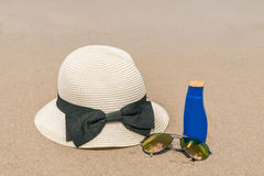 Occhiali da sole, crema del sole e cappello sulla spiaggia di sabbia bianca Fotografie Stock
